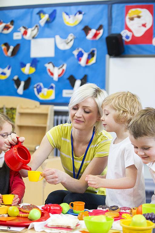 Erzieherin spielt mit Kinder