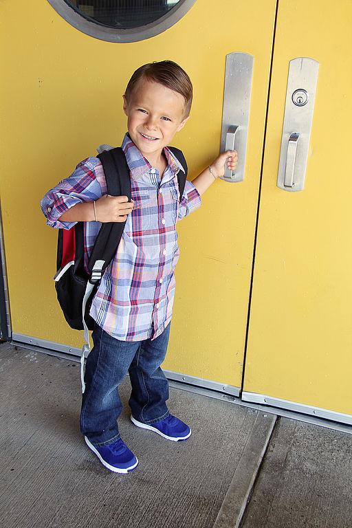Junge öffnet Schultür