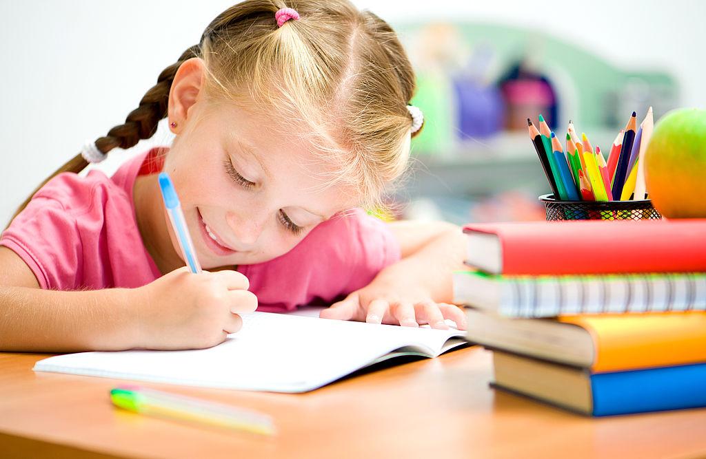 Mädchen schreibend in Klassenraum