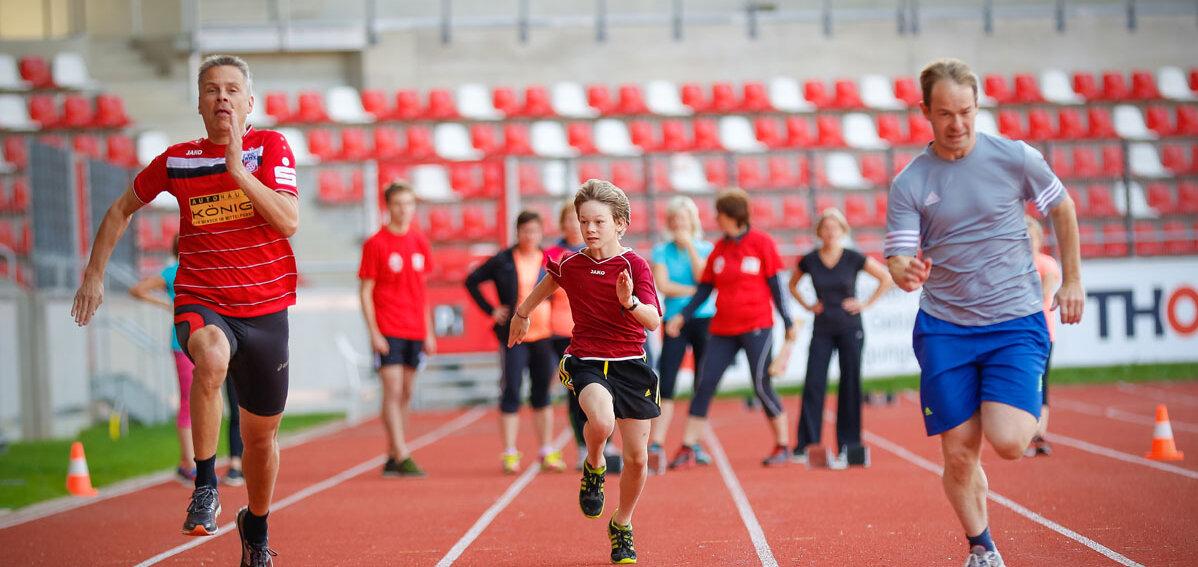 Läufer aller Altersklassen auf einer Sprintbahn