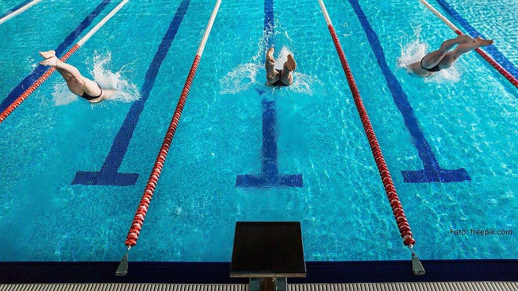 drei Schwimmsportler springen vom Startblock