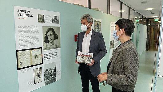 Minister und Staatssekretärin betrachten Ausstellungsplakat
