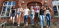 Fröhliche Schüler auf eirn Treppe vor einem Schulgebäude