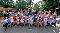 Gruppenbild: viele Kinder mit Minister und STIFT-Vertretern