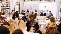 Blick in den Seminarraum, junge Leute hören einen Vortrag
