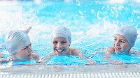 drei Jungs mit Badekappen planschen am Beckenrand