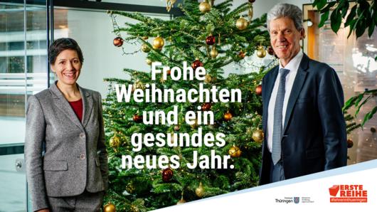 Minister und Staatssekretärin vor einem geschmücktem Weihnachtsbaum