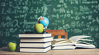Schulbücher auf Schulbank vor Tafel
