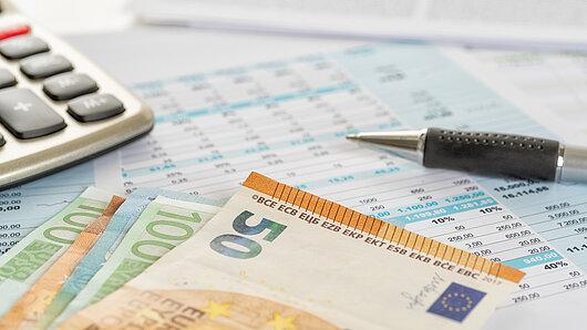 Taschenrechner, Geldscheine und Stift