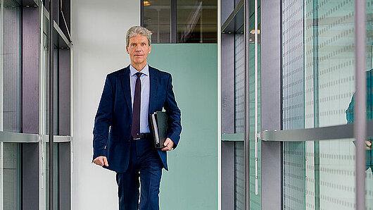 Minister Holter in einem modernen Büroflur