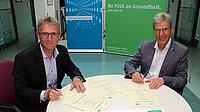 Zwei Herren unterzeichnen eine Vereinbarung