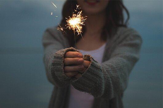 Hände mit einer brenden Wunderkerze im Hintergrund eine Frau verschwommen