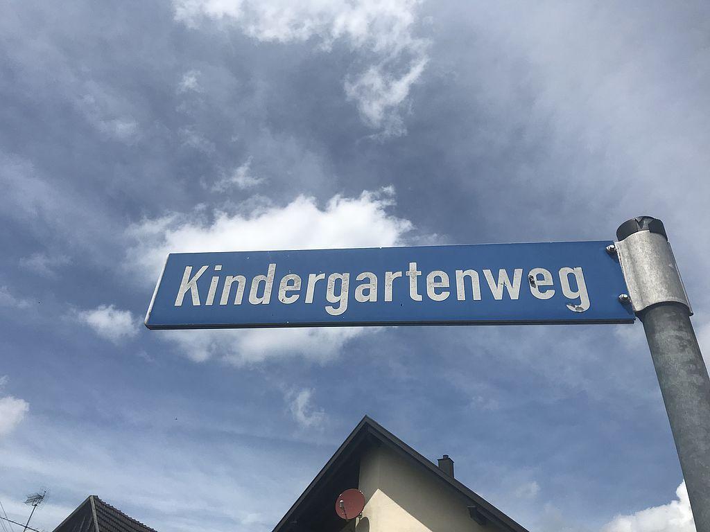 """Straßenschuld """"Kindergartenweg"""" vor blauem Himmel mit Wolken"""
