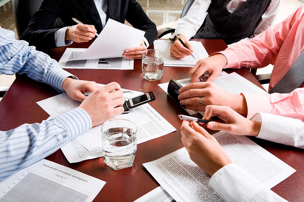 Fünf Personen sitzen an einem Tisch mit Papieren und Stiften und halten eine Besprechung ab
