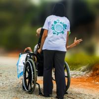 Helfer schiebt Rollstuhl