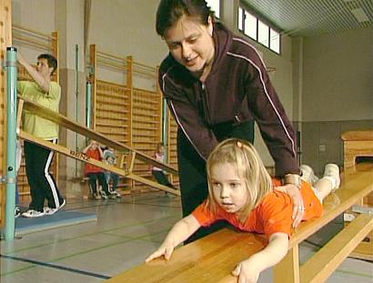 Lehrerin und Kind in Turnhalle
