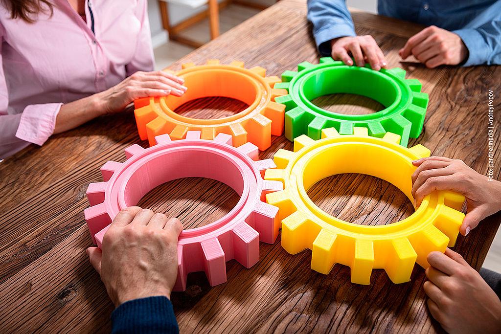 Symbolbild mit Zahnrädern uns Hände, die siese steuern