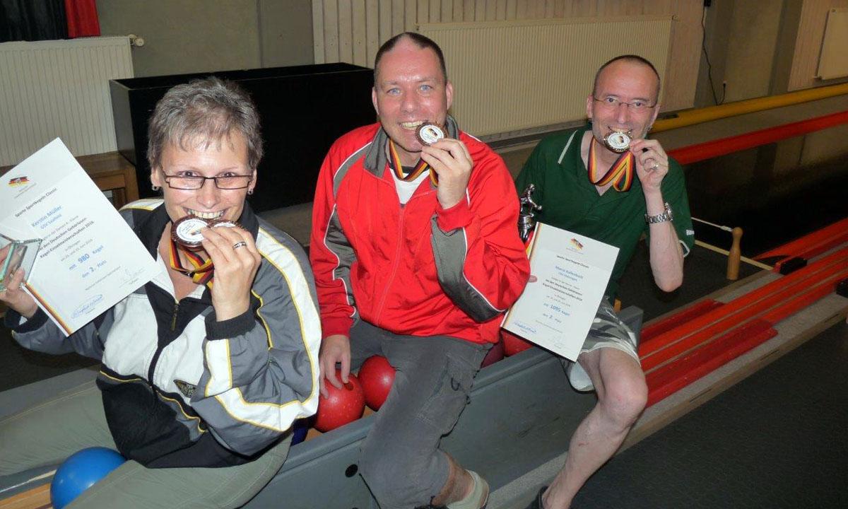 Drei Kegler freuen sich über Medaillen