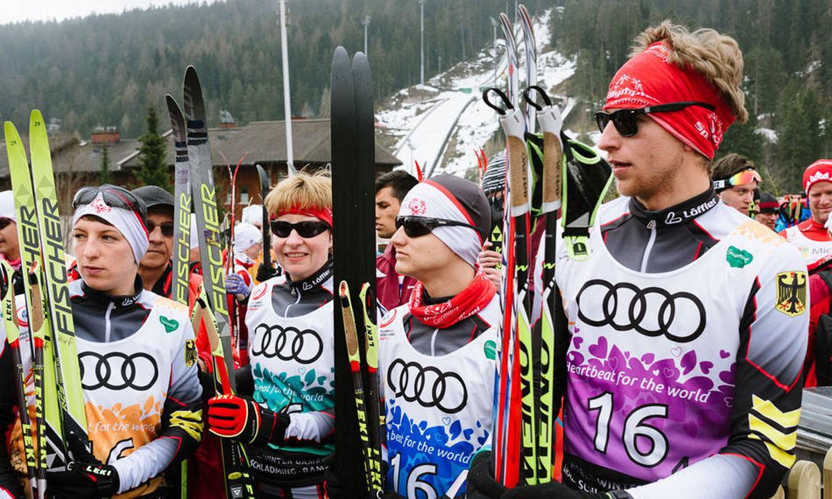Vier Sportlerinnen und Sportler in Wintersportkleidung