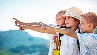 drei Kinder zeigen mit ihren Fingern in die Natur
