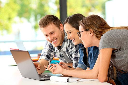 Drei Schüler surfen mit einem Laptop