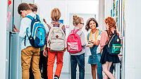 Schulkinder mit Rucksäcken auf einem Flur