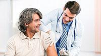 Arzt impft männlichen Patienten