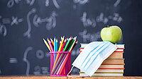 Maske, Stifte, Bücher und ein Apfel vor eine Schultafel