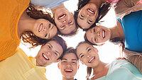 sieben junge Menschen lachend und im Kreis stehend