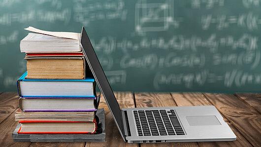 Laptop und Bücherstapel vor einer Kreidetafel