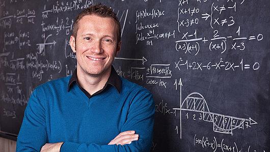 Lehrer vor einer Tafel mit mathematischen Formeln