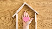 Kinderhand mit Herz in einem symbolischen Haus aus Holzklötzchen